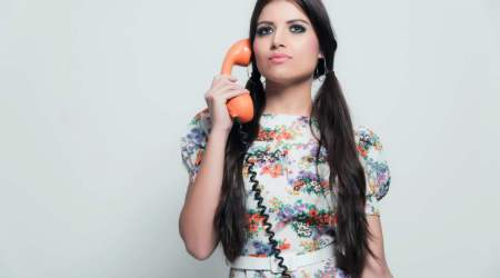 Retro 70s fashion. Pretty brunette girl with long hair. Calling with orange phone. Studio shot against white.