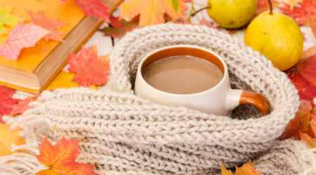 Cup of coffee and warm scarf on wooden background with maple lea